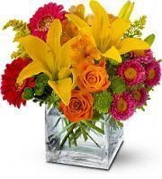 Orange roses and alstroemeria, yellow Asiatic lilies, pink Matsumoto asters, hot pink miniature gerberas and green button spray chrysanthemums – accented with oregonia and solidaster