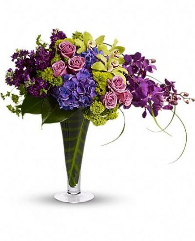 Bountiful blooms including purple hydrangea, green cymbidium orchids, purple mokara orchids, lavender roses, green viburnum, green button spray mums and purple stock are elegantly mixed with greens such as bupleurum, calathea leaves, philodendron leaves and lily grass in a tall, footed flare vase.