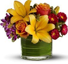 lilies, roses, alstroemeria, leaf-lined vase, fresh greenery, peach, orange, purple, red