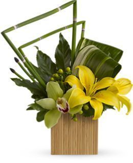 "The artistic bouquet includes yellow Asiatic lilies, green cymbidium orchids and green hypericum accented with assorted greenery and delivered in a 4 1/2"" contemporary cube vase."